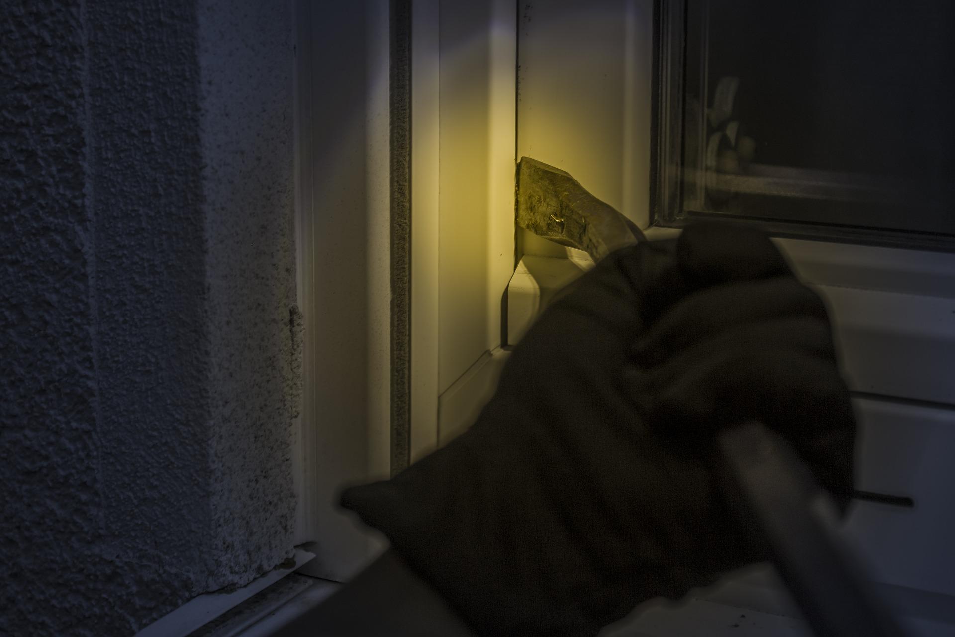 Włamywacz otwierający okno